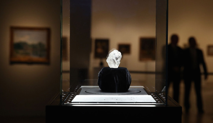 """NEW YORK, NY - MAY 04:  The 1109-carat rough Lesedi La Rona diamond, the biggest rough diamond discovered in more than a century, sits in a display case at Sotheby's on May 4, 2016 in New York City. The stone was found by Lucara Diamond Corp. last year at its Karowe mine in Botswana. The diamond, which is nearly the size of a tennis ball at 66.4 x 55 x 42mm and is believed to be about 2.5 billion to 3 billion years old, was named  """"Our Light"""" in the local Tswana language. Lesedi La Rona will be offered at auction in London on June 29 and be on display at Sotheby's New York. The diamond could sell for $70 million or more.  (Photo by Spencer Platt/Getty Images)"""