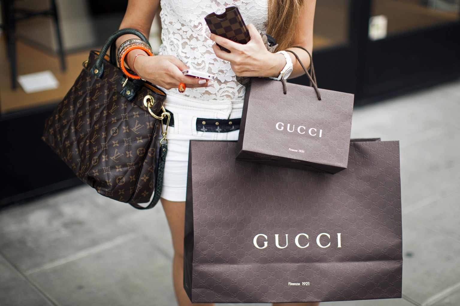 A pedestrian carries Gucci-branded shopping bags and a Louis Vuitton SA handbag as she walks along the Rue du Rhone in Geneva, Switzerland, on Saturday, June 9, 2012. Swiss economic growth unexpectedly accelerated in the first quarter, led by consumer demand. Photographer: Valentin Flauraud/Bloomberg via Getty Images